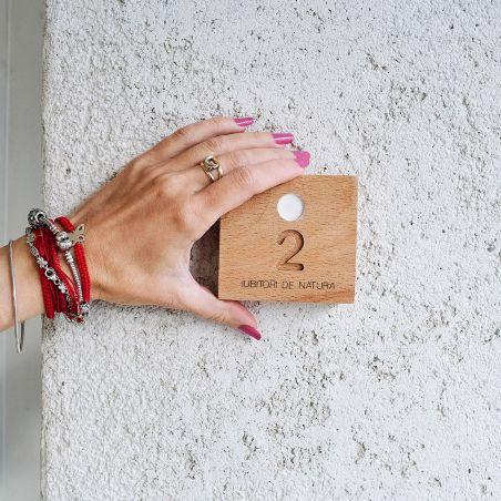 mână care ține numar apartament din lemn masiv de fag